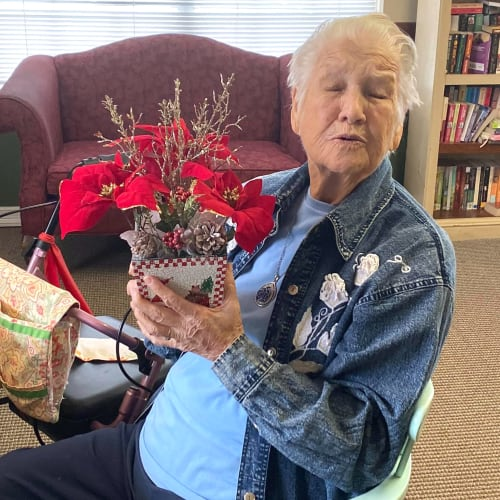 Smiling resident holding a bouquet of flowers at Canoe Brook Assisted Living in Duncan, Oklahoma