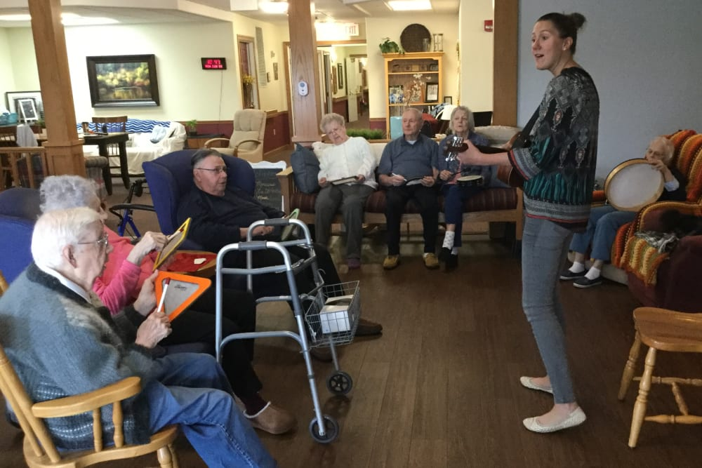 Staff member and residents playing the guitar at Prairie Hills Independence in Independence, Iowa.