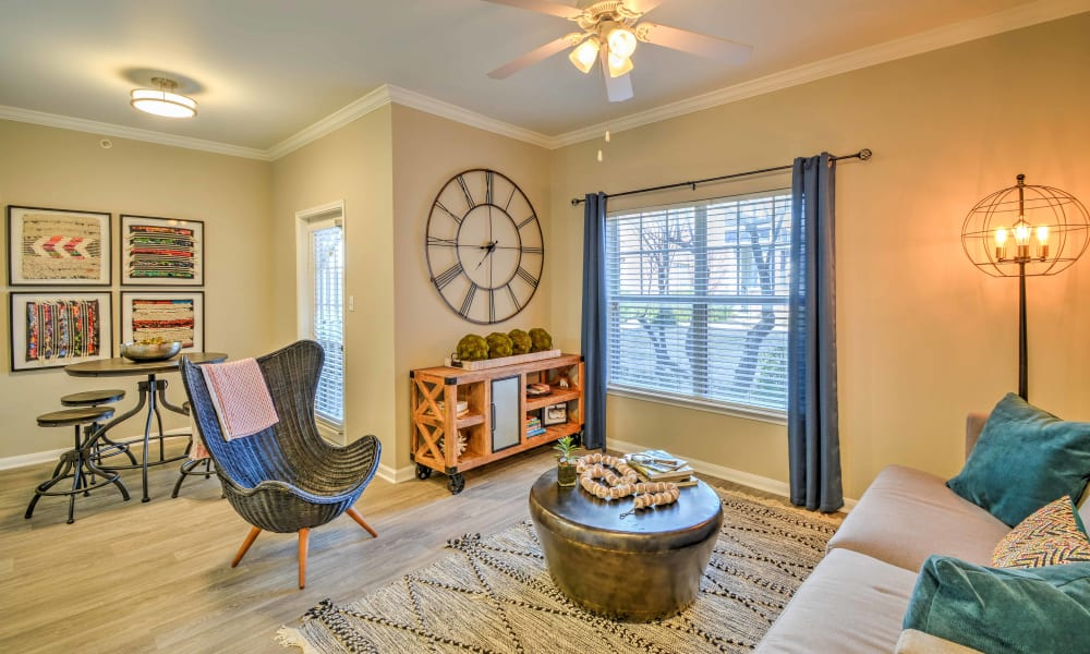 A modern living room layout with big sunlit windows at The Atlantic Station in Fort Worth, Texas