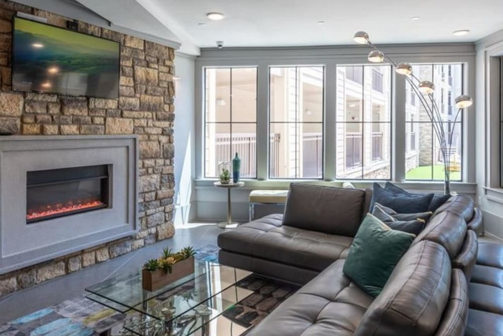 Cozy sitting area in front of a fireplace in the resident clubhouse at Heights West 11th in Houston, Texas