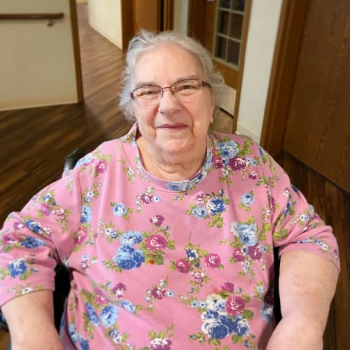 Sitting resident smiling at the camera inside The Oxford Grand Assisted Living & Memory Care in McKinney, Texas