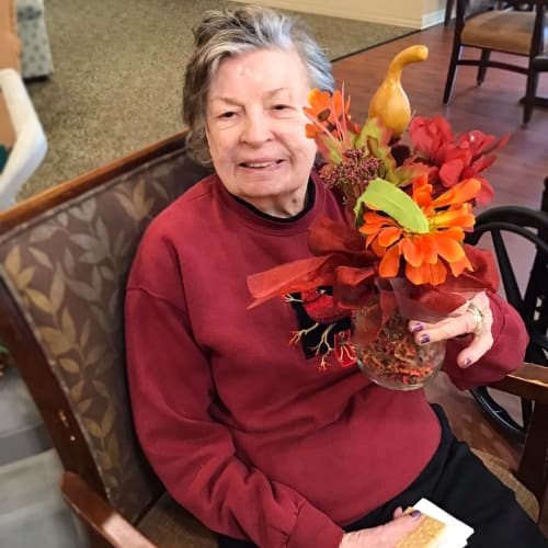 Resident with a festive plant arrangement at Oxford Glen Memory Care at Grand Prairie in Grand Prairie, Texas