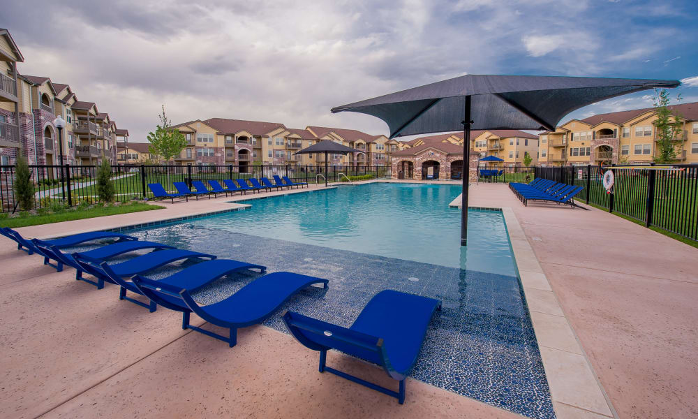 Sparkling swimming pool with poolside seating at Watercress Apartments in Maize, Kansas