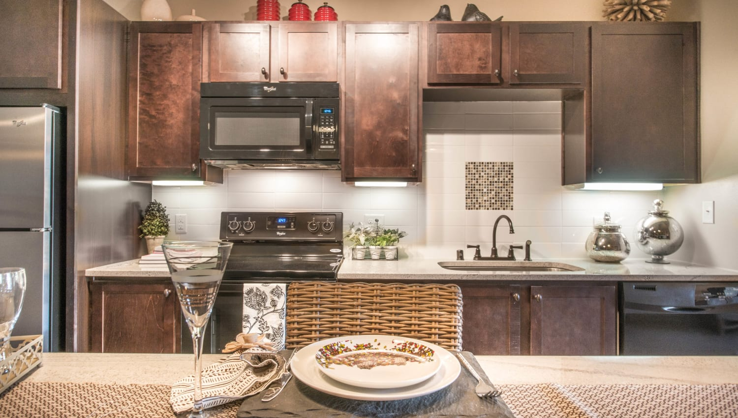 Dark wood cabinetry and granite countertops in a model home's kitchen at Union At Carrollton Square in Carrollton, Texas