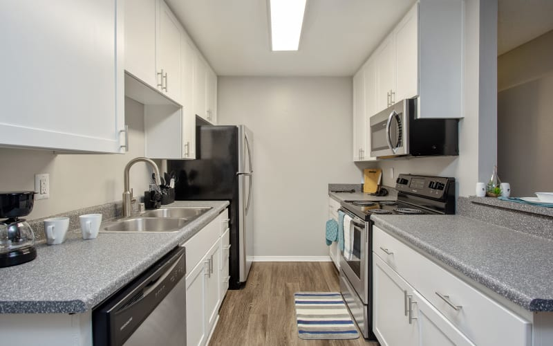 White cabinets in a renovated kitchen with stainless steel appliances at Shadow Ridge Apartments in Oceanside, California