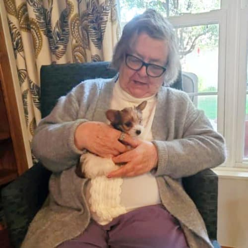 A resident holding a very small dog at Creekside Village in Ponca City, Oklahoma