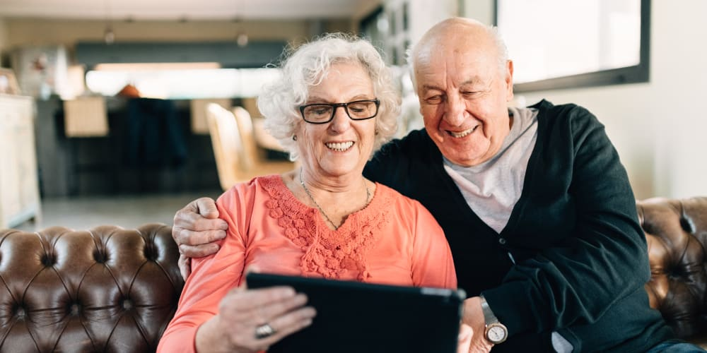 Resident couple looking at a tablet together at The Springs at Lake Oswego in Lake Oswego, Oregon