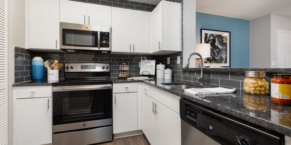 Large kitchen with white cabinets and stainless steel appliances at Beach Walk at Sheridan in Dania Beach, Florida