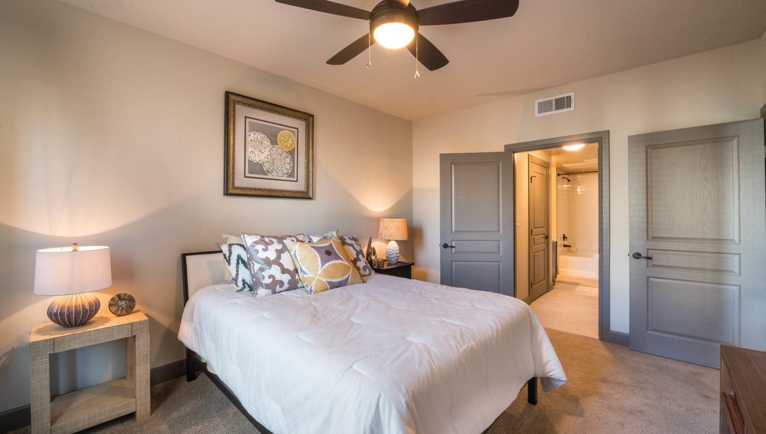 Ceiling fan and plush carpeting in a model home's master bedroom at Union At Carrollton Square in Carrollton, Texas