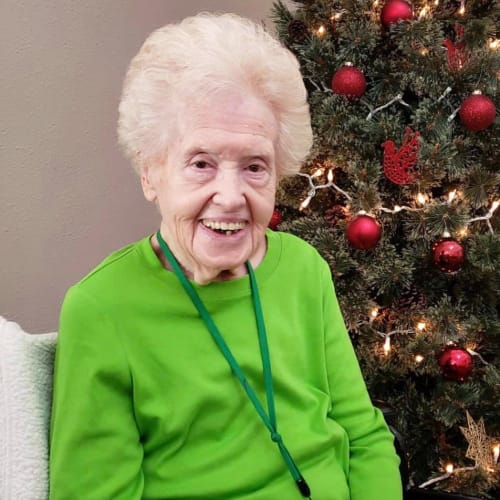 A resident in front of a christmas tree at Canoe Brook Assisted Living in Broken Arrow, Oklahoma