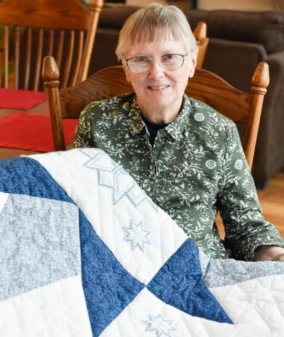 Resident showing off her quilt she made at Garden Place Red Bud in Red Bud, Illinois.