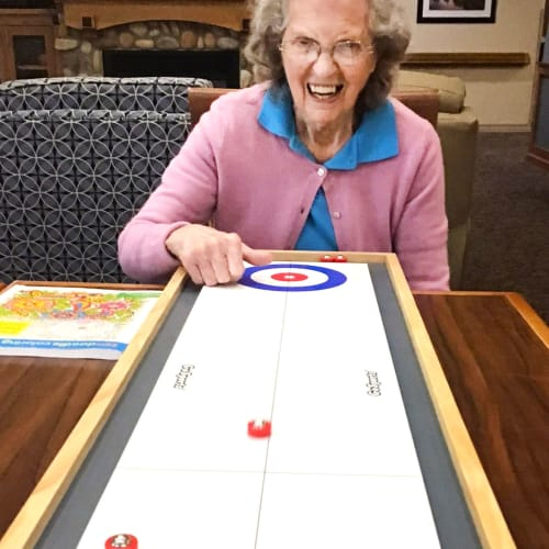 Resident playing shuffleboard at Glen Carr House Memory Care in Derby, Kansas