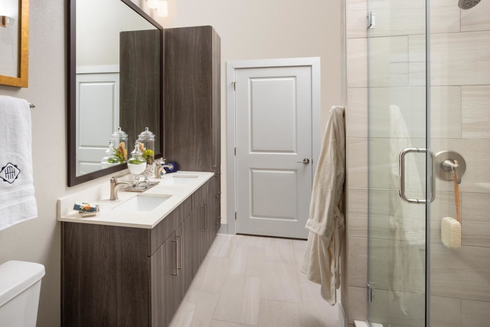 Large vanity mirror and a stand-up shower in a model home's bathroom at Magnolia Heights in San Antonio, Texas