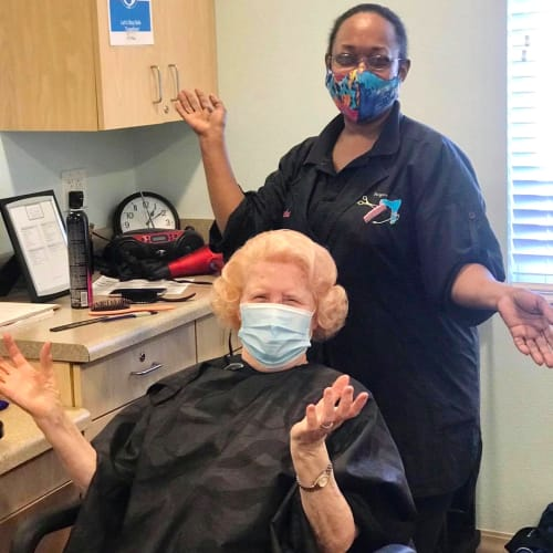 Masked Caregiver giving a haircut at Oxford Glen Memory Care at Carrollton in Carrollton, Texas