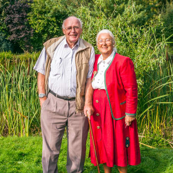 Resident couple pose for the camera in a field near at The Iris Senior Living in Great Falls, Montana