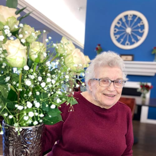 Assisted Living resident smiling with flowers at Madison House in Norfolk, Nebraska