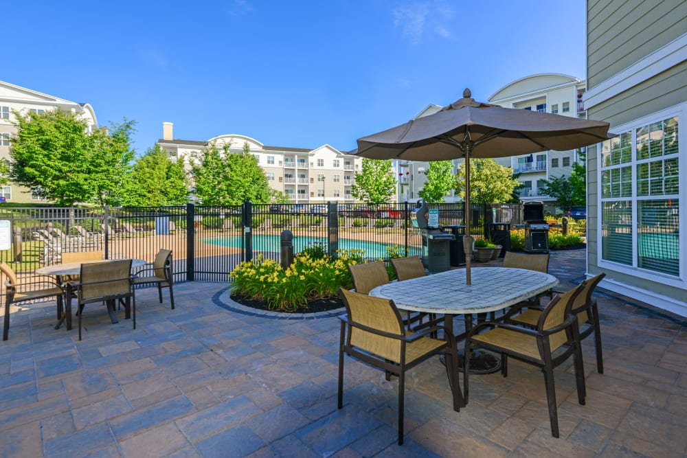 Umbrella covered tables and chairs on pool deck at Sofi Danvers in Danvers, Massachusetts