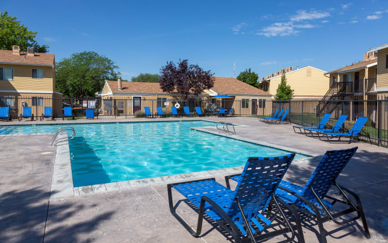 Lounge chairs by the brilliant blue pool at Callaway Apartments in Taylorsville, Utah