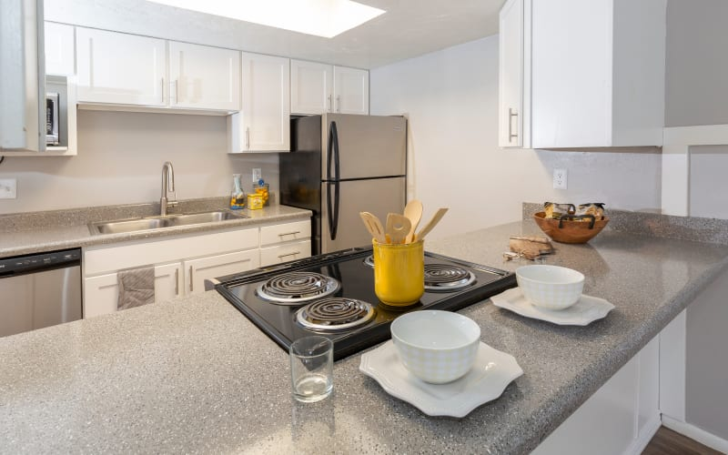 Renovated kitchen with white cabinets and ample counter space at Windgate Apartments in Bountiful, Utah