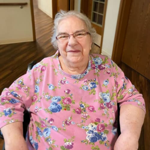 A happy resident sitting inside of The Oxford Grand Assisted Living & Memory Care in McKinney, Texas