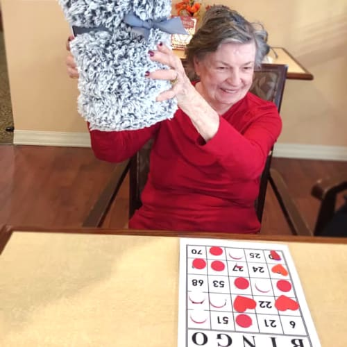 Resident holding a blanket she won at bingo at Oxford Glen Memory Care at Grand Prairie in Grand Prairie, Texas