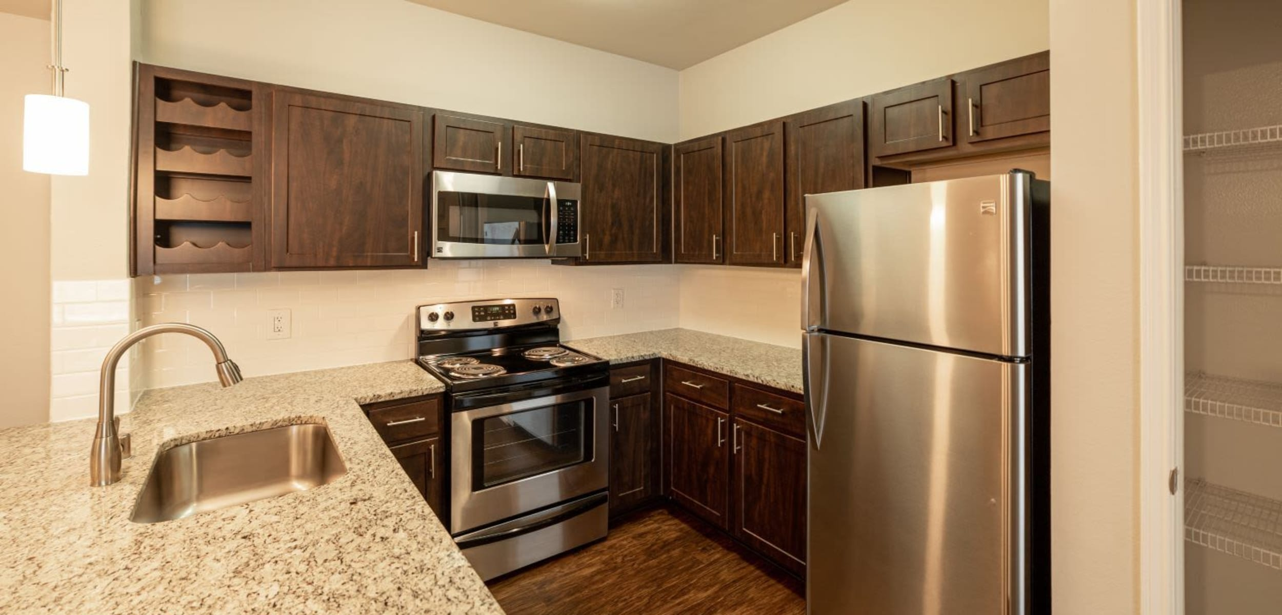 Modern kitchen with stainless steel appliances at Marquis at Stonebriar in Frisco, Texas