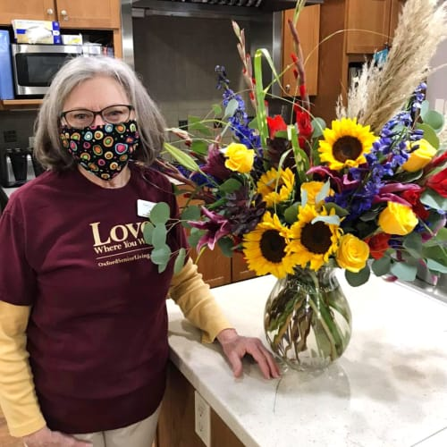 A resident standing next to a flower arrangement at Glen Carr House Memory Care in Derby, Kansas