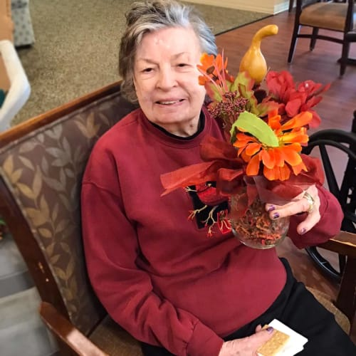 Resident holding a fall-themed flower arrangement at Oxford Glen Memory Care at Grand Prairie in Grand Prairie, Texas