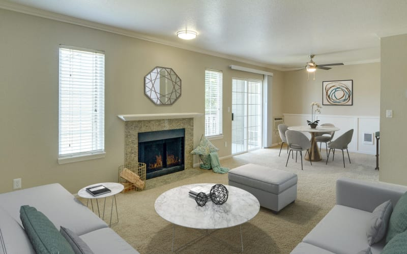 Spacious living room and dining room with a fireplace, ceiling fan and patio access at Carriage House Apartments in Vancouver, Washington