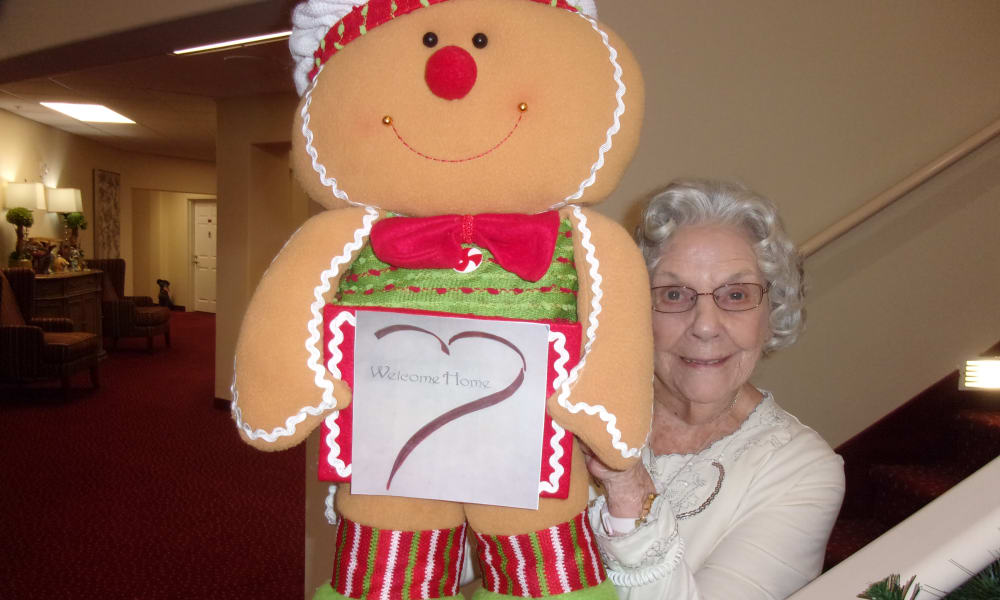 Resident holding an oversized, stuffed gingerbread man at Camden Springs Gracious Retirement Living in Elk Grove, California