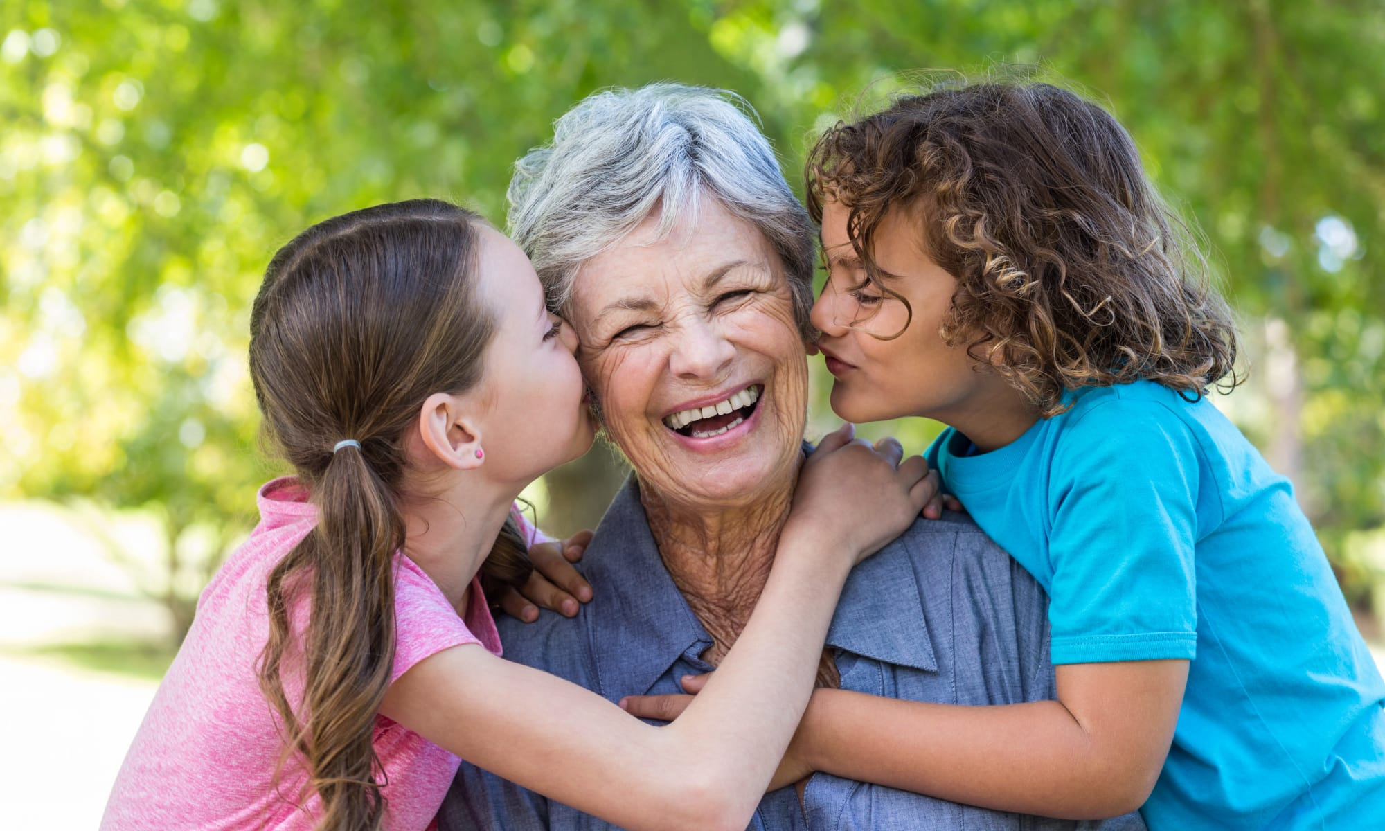 Resident laughing with her grand-kids at Avenir Memory Care at Scottsdale in Scottsdale, Arizona.
