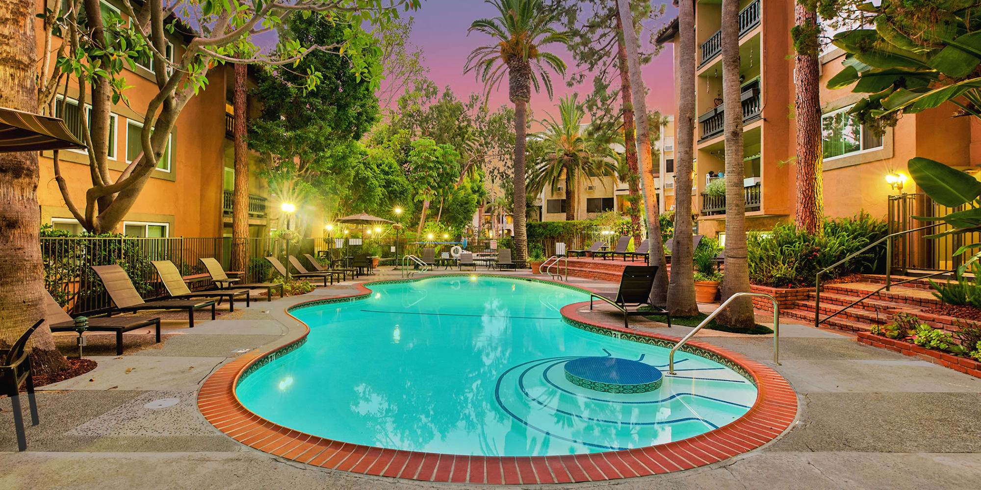 Early twilight at the swimming pool area surrounded by palm trees and lounge chairs at Casa Granada in Los Angeles, California