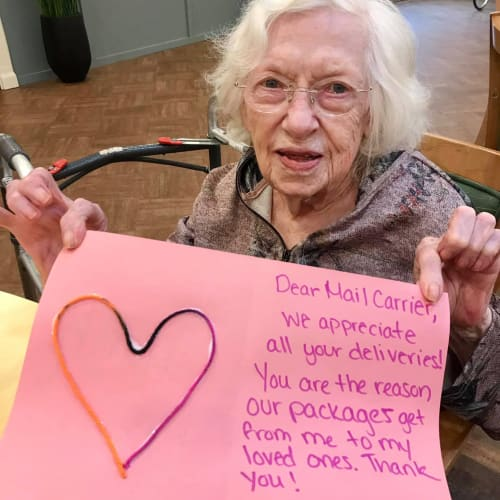 A resident holding a thank you letter for the mailman at Oxford Glen Memory Care at Carrollton in Carrollton, Texas