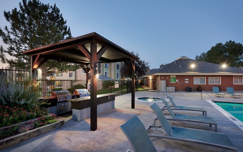 Covered barbecue area near the swimming pool at dusk at Alton Green Apartments in Denver, Colorado