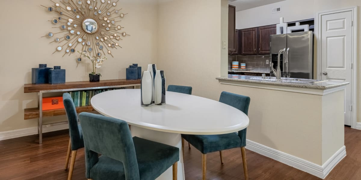 Round dining table and chairs overlooking kitchen at Marquis at Kingwood in Kingwood, Texas