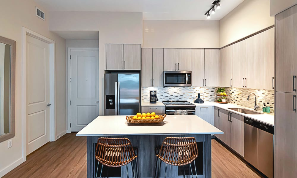 Light cabinets with wood style flooring in the kitchen around the large island at 6600 Main in Miami Lakes, Florida