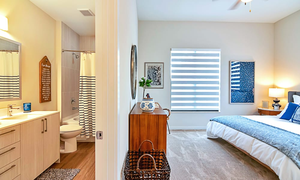 Bedroom and own bathroom in the room with a ceiling fan in model home at 6600 Main in Miami Lakes, Florida