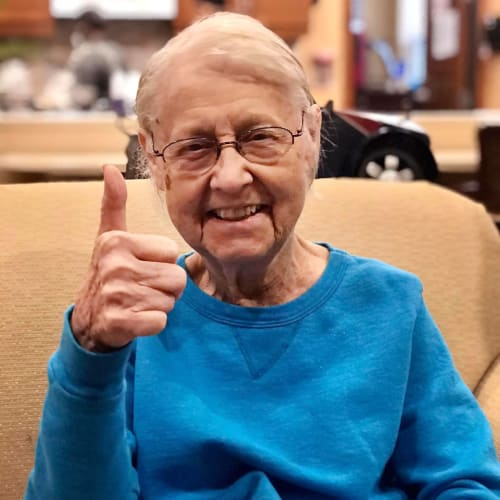 Smiling resident giving a 'thumbs up' at Oxford Glen Memory Care at Carrollton in Carrollton, Texas