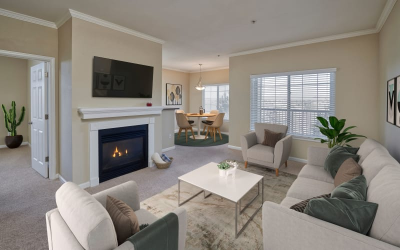 Elegant living room with a fireplace and large windows at Skyecrest Apartments in Lakewood, Colorado