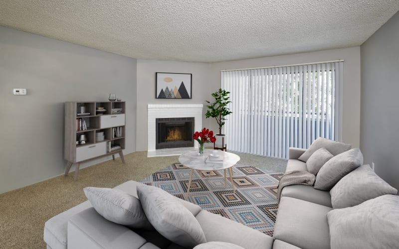 Spacious and bright living room with a fireplace at Alton Green Apartments in Denver, Colorado