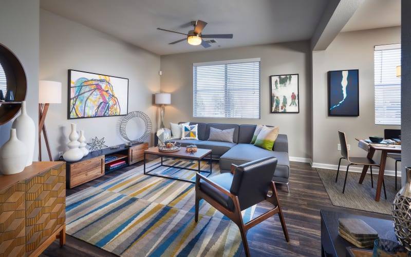 A furnished living room with blue accents at The Rail at Inverness in Englewood, Colorado