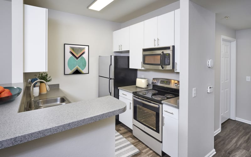Renovated kitchen with stainless steel appliances and white cabinets at Bear Valley Park in Denver, Colorado