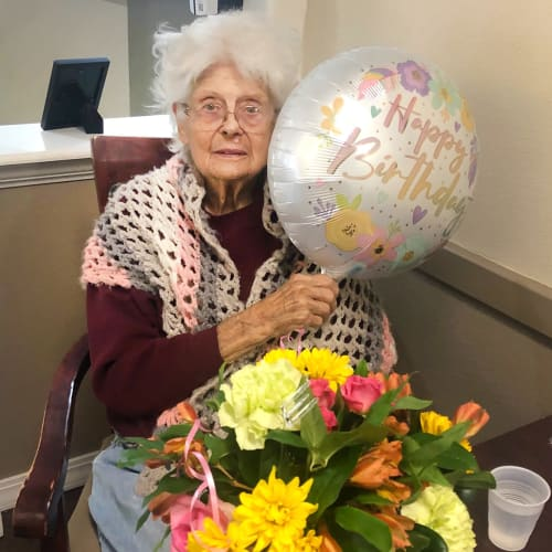 Resident celebrating her birthday with gifts of flowers and balloons at Madison House in Norfolk, Nebraska