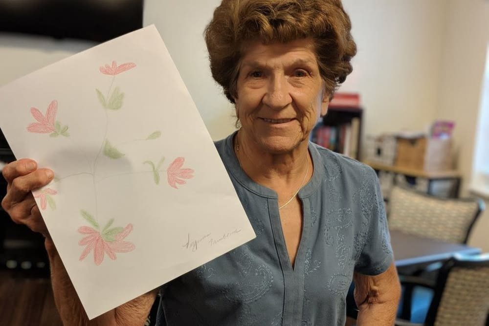 A female resident showing off her floral artwork at Springview Manor in Lima, Ohio
