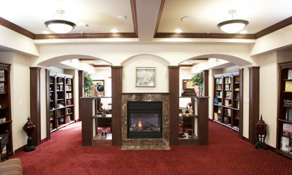 Library with seating in front of the fireplace at Camden Springs Gracious Retirement Living in Elk Grove, California