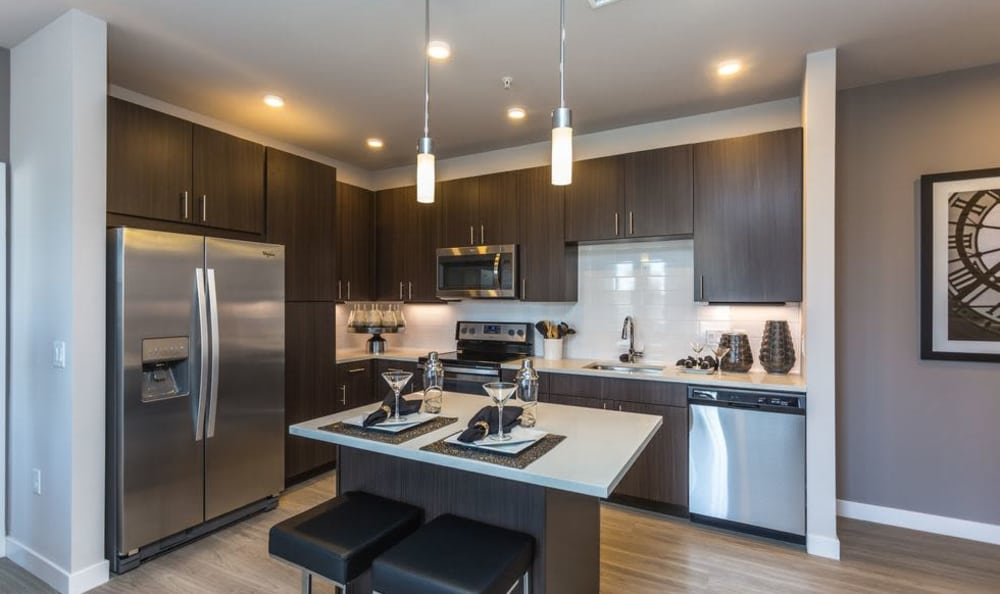 Brown spec Kitchen cabinetry with kitchen island and stainless steel appliances at Strata Apartments