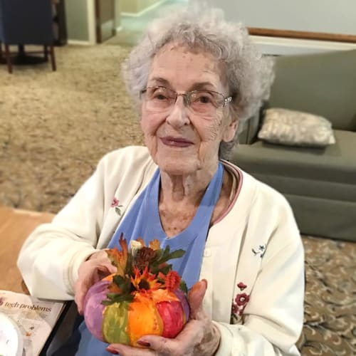 A resident holding a painted pumpkin at Canoe Brook Assisted Living & Memory Care in Catoosa, Oklahoma