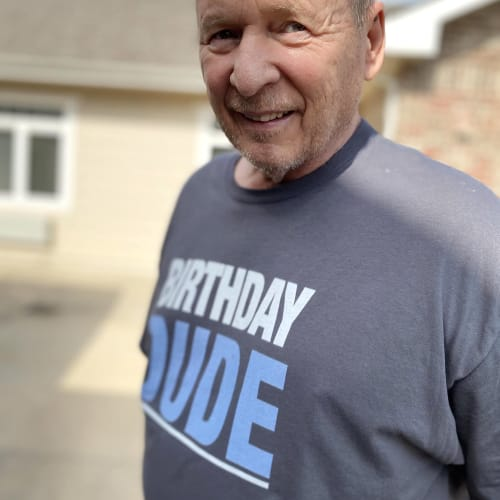 A resident wearing a shirt that says 'birthday dude' outside at Oxford Glen Memory Care at Carrollton in Carrollton, Texas