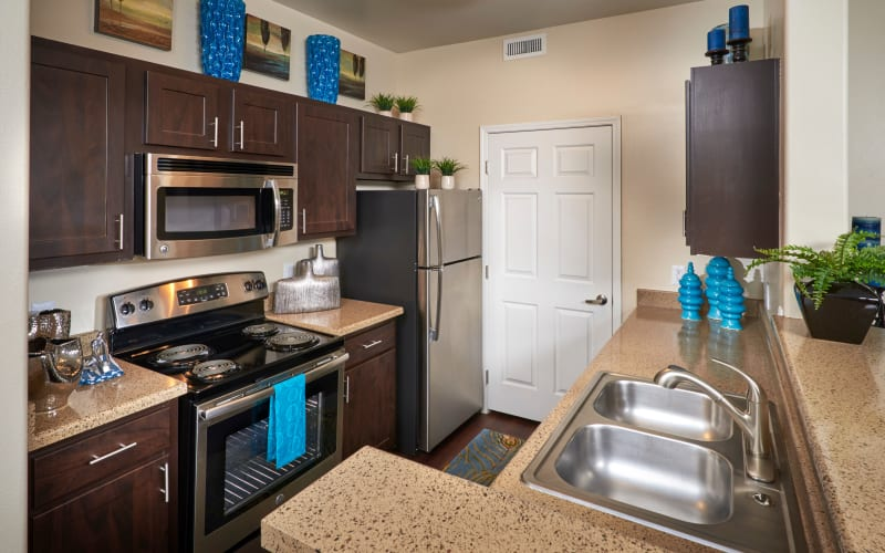 Well organized, renovated kitchen with brown cabinets at Promenade at Hunter's Glen Apartments in Thornton, Colorado