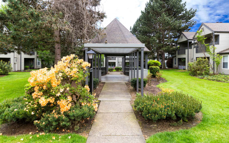 Lush landscaping around a gazebo at Meadows at Cascade Park Apartments in Vancouver, Washington